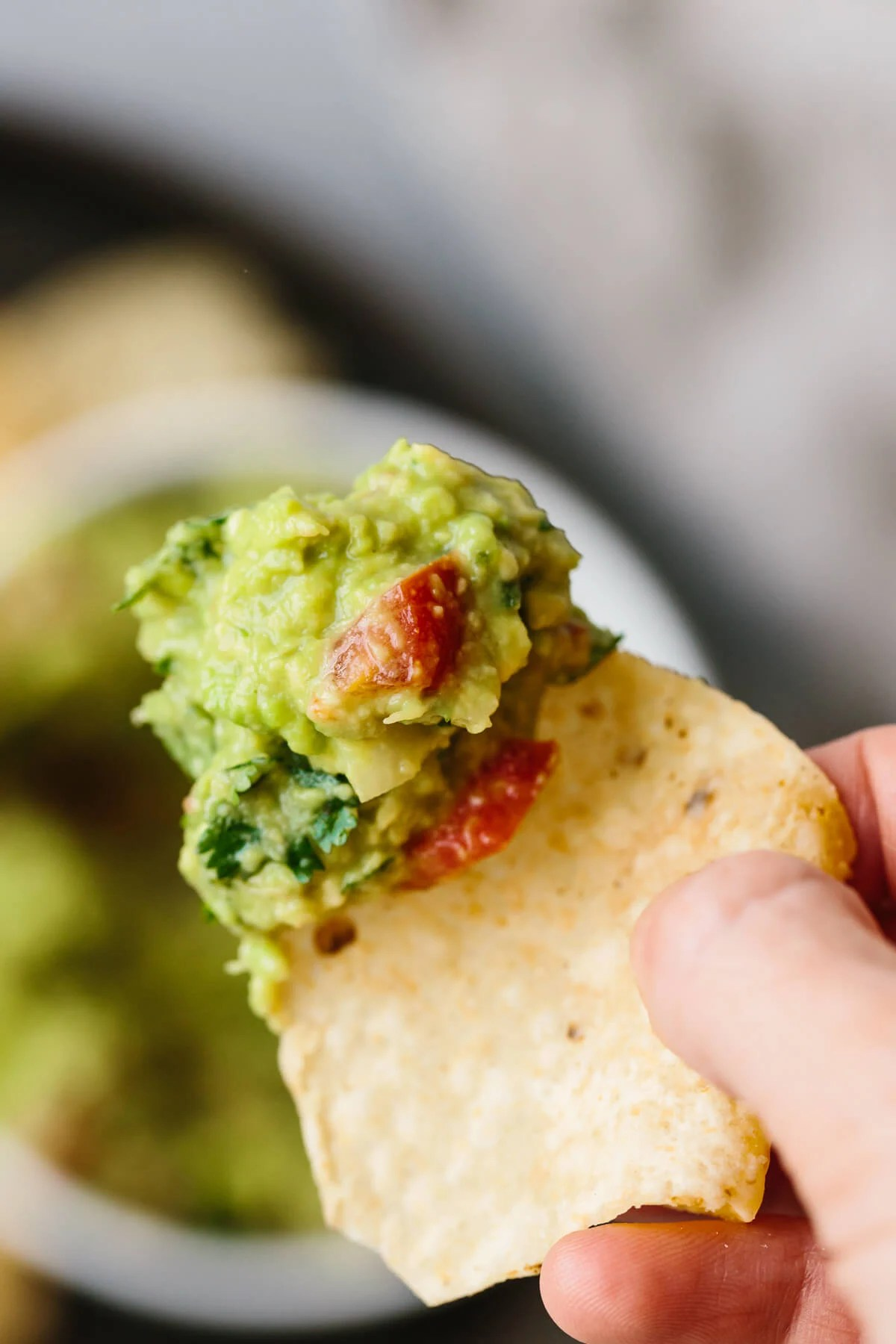 A scoop of guacamole on a tortilla chip.
