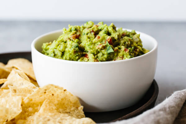 Guacamole in a serving bowl next to tortilla chips.