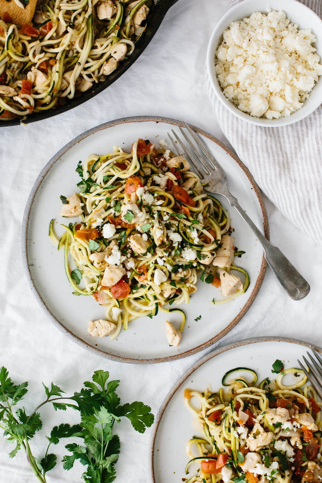 Zucchini noodles with chicken and pico de gallo on a white plate.