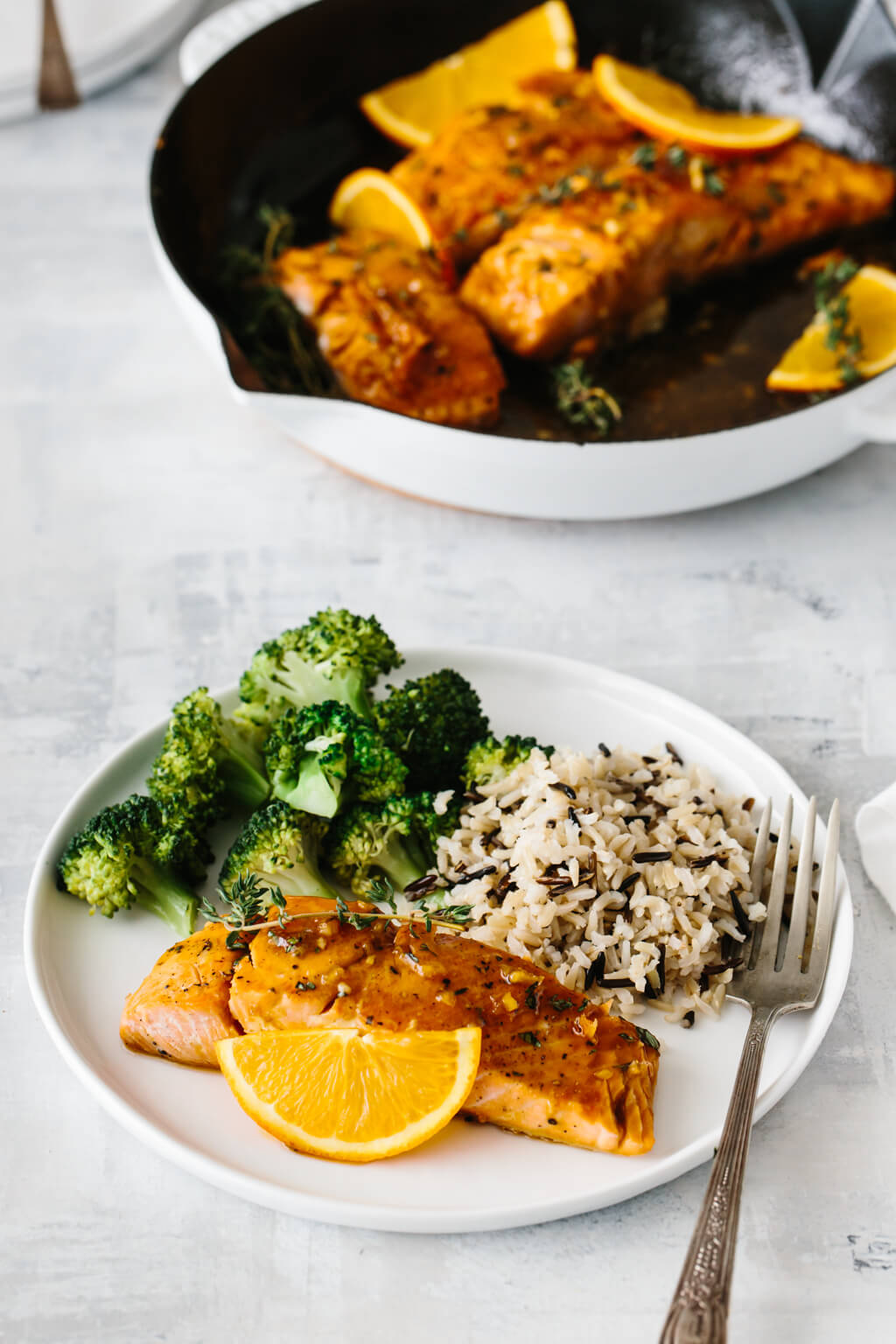 A white plate with salmon, rice and broccoli.