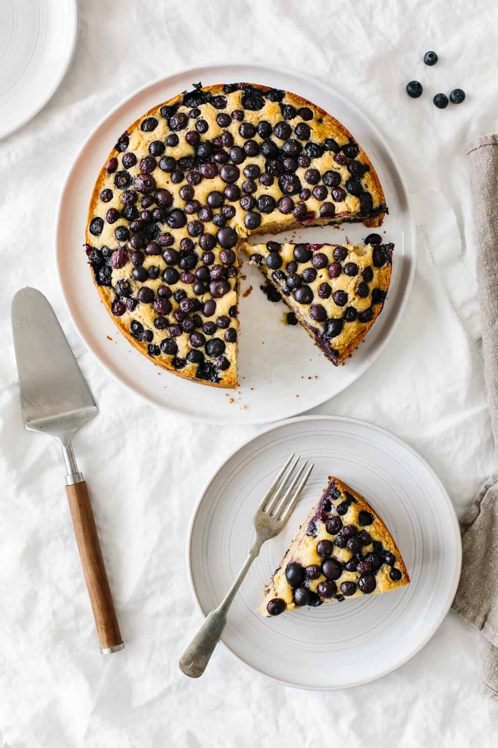 A lemon cake topped with blueberries on a table. A slice of the cake is taken from the cake and on a plate next to it.