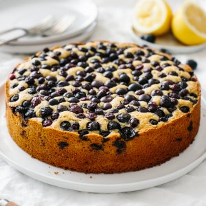 A lemon cake topped with blueberries on a table.