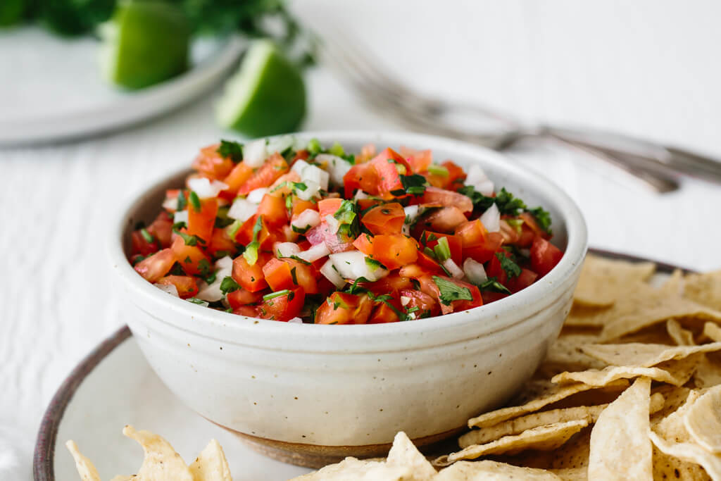 Pico de gallo salsa in a bowl surrounded with corn tortilla chips and a lime wedge.