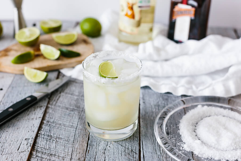 Margarita in a glass on a wood table with alcohol in the background.