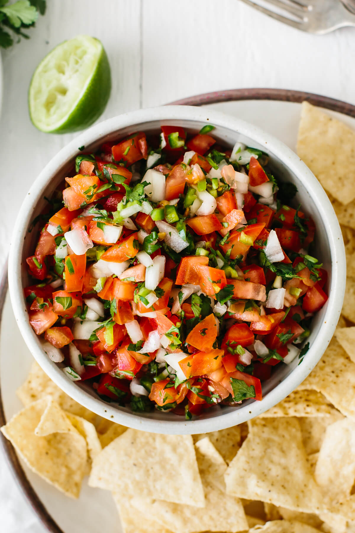 Pico de gallo in a bowl next to chips.