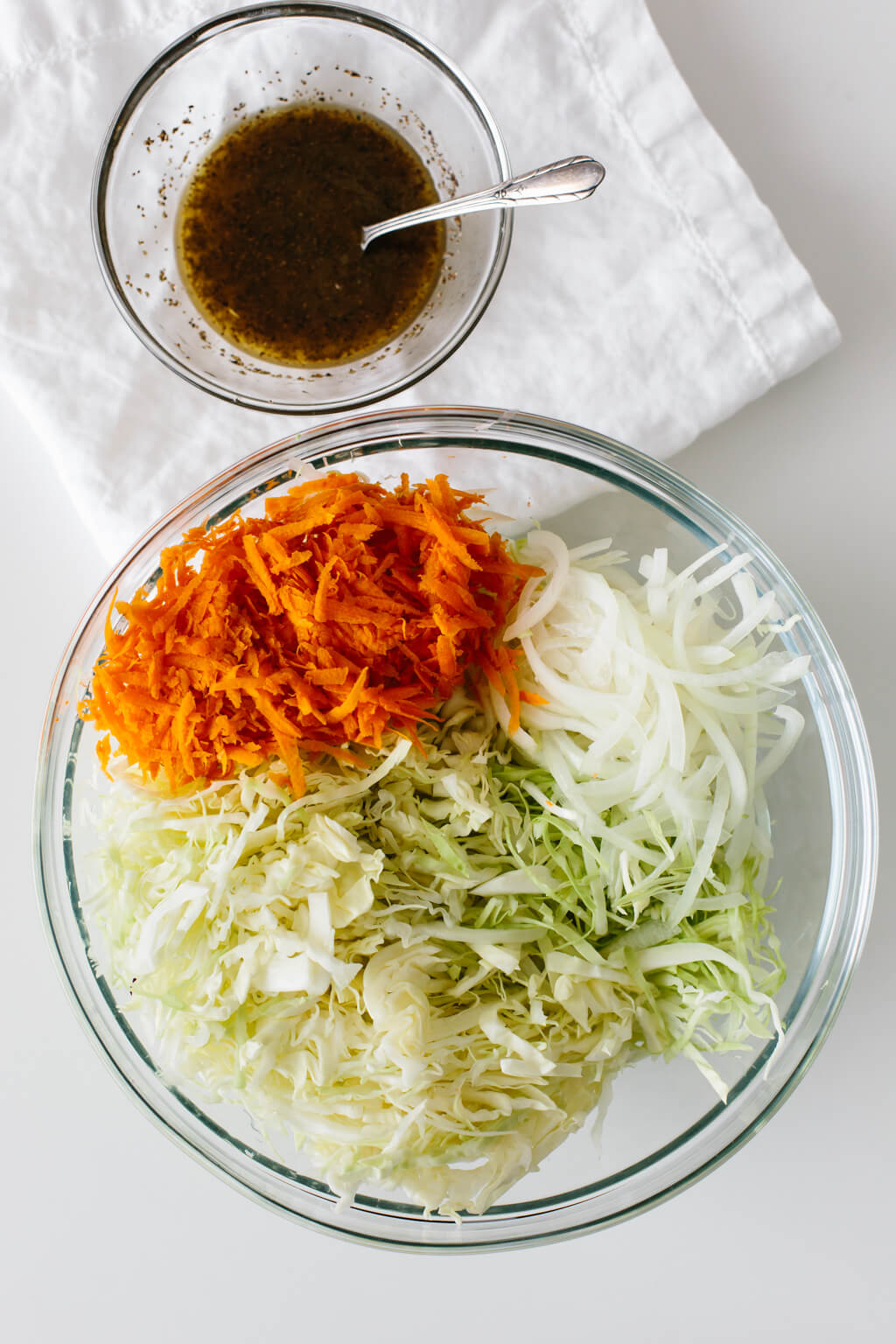 Vinegar coleslaw ingredients in a mixing bowl with dressing on the side.