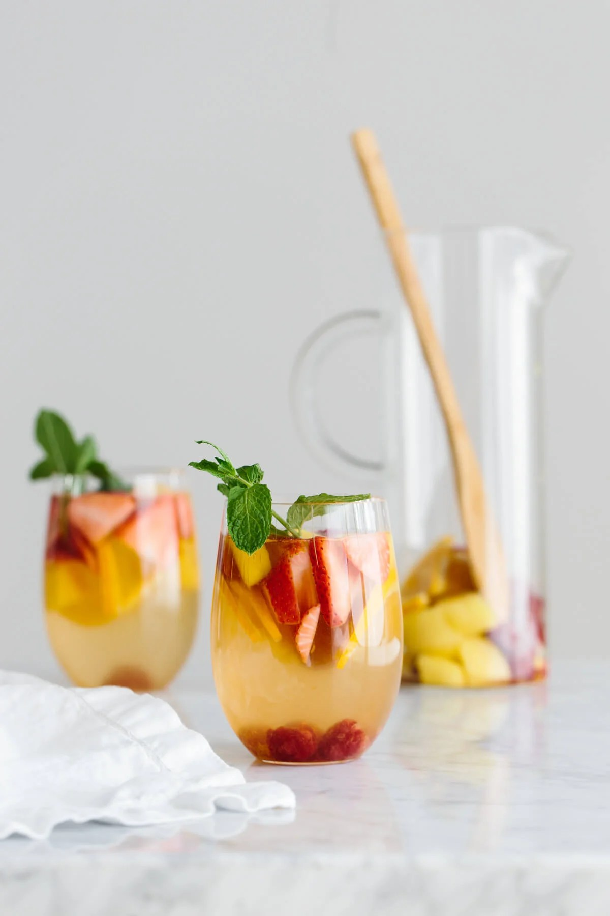 Two glasses of white sangria with an empty pitcher in the background.