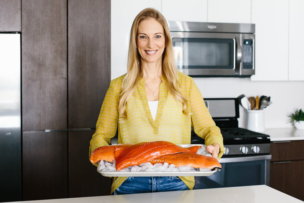 Girl in kitchen holding sockeye salmon and king salmon on a platter.