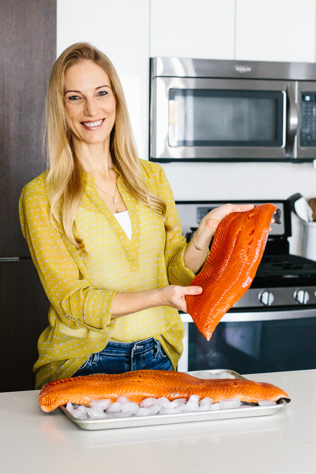 Girl holding sockeye salmon filet in a kitchen.