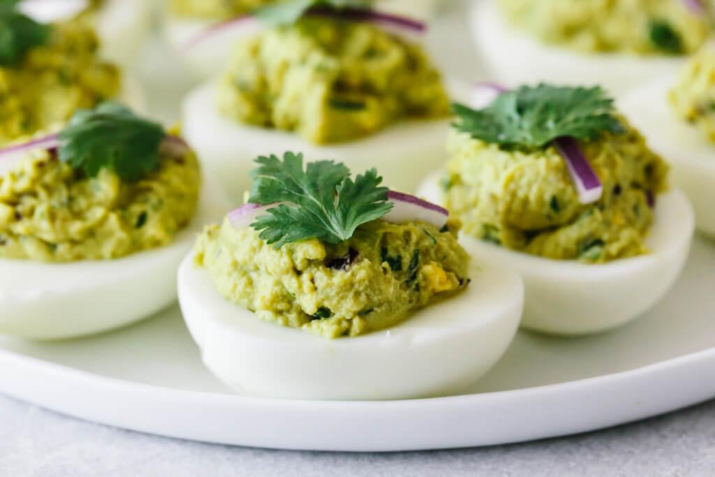 Avocado deviled eggs on a white plate.