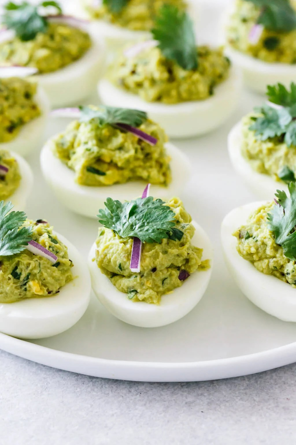 Several avocado deviled eggs on a white plate.