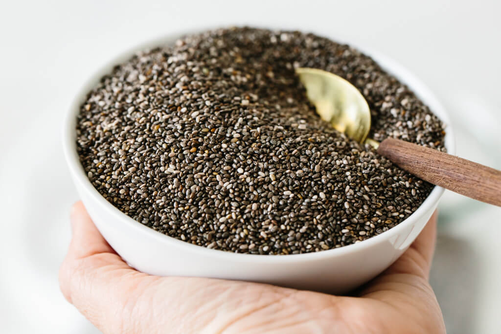 Chia seeds in a white bowl held in hand.