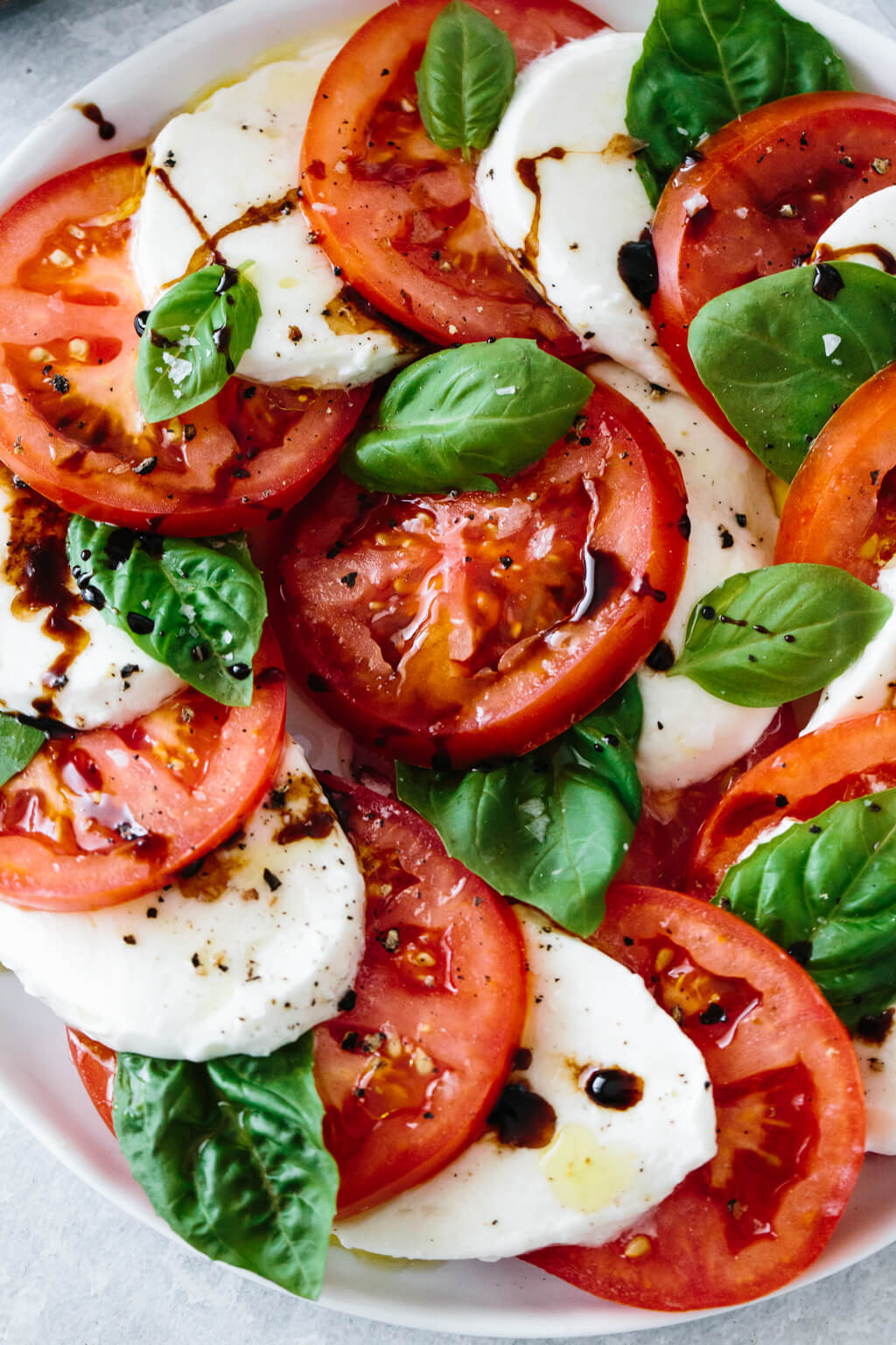 Slices of tomato and mozzarella on a plate with fresh basil leaves.