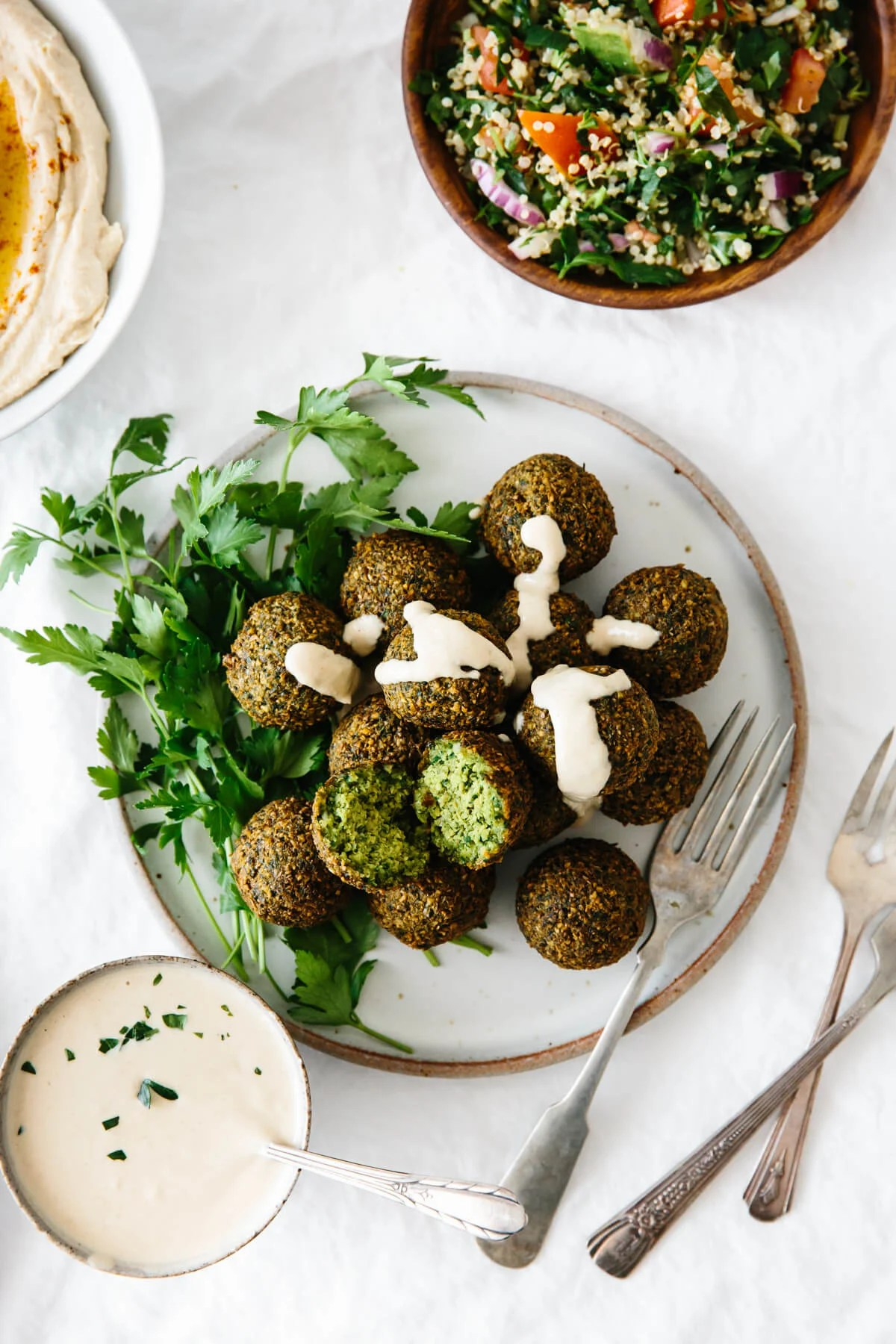 A plate of falafel next to hummus, tahini sauce, and salad.