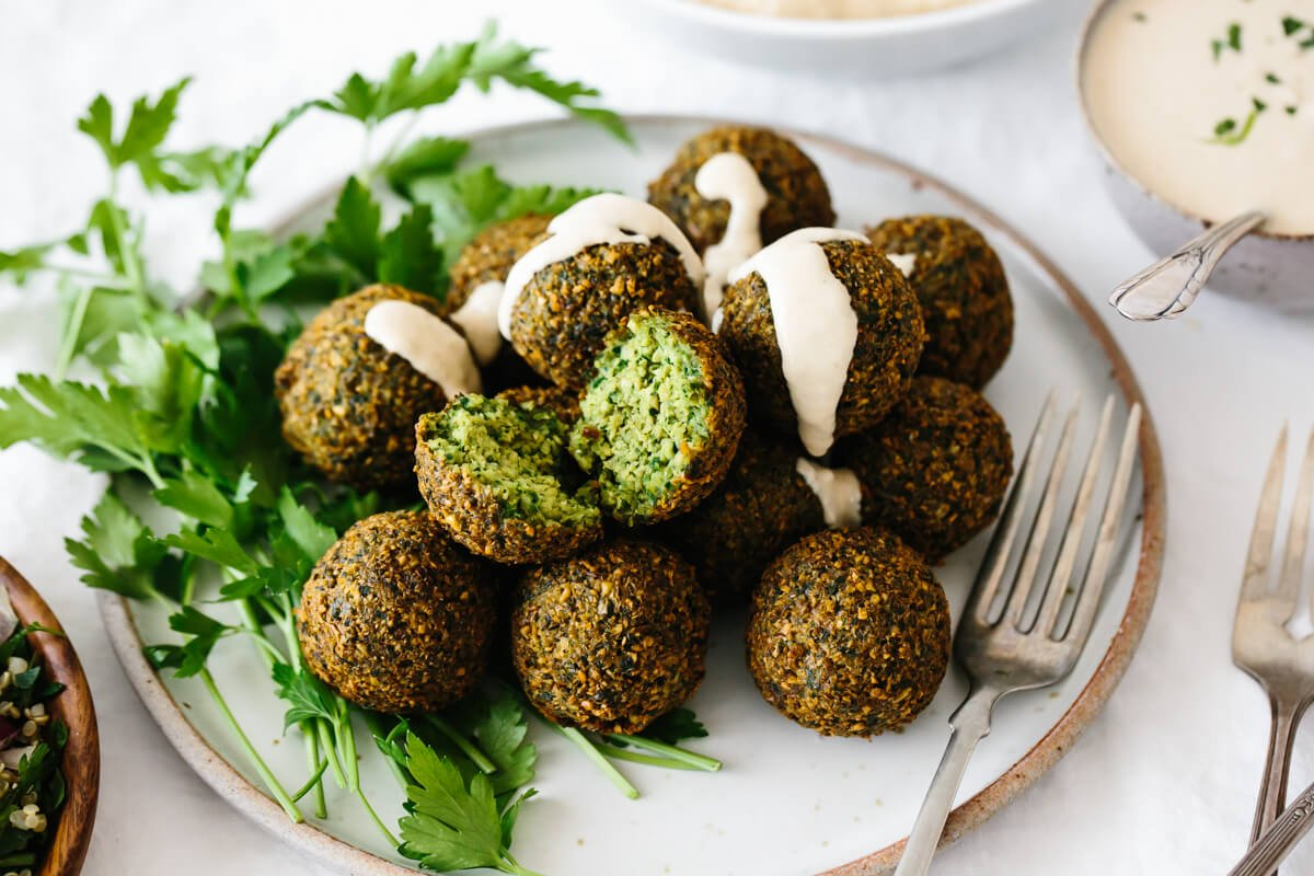 Several falafel balls on a plate garnished with parsley and tahini sauce.