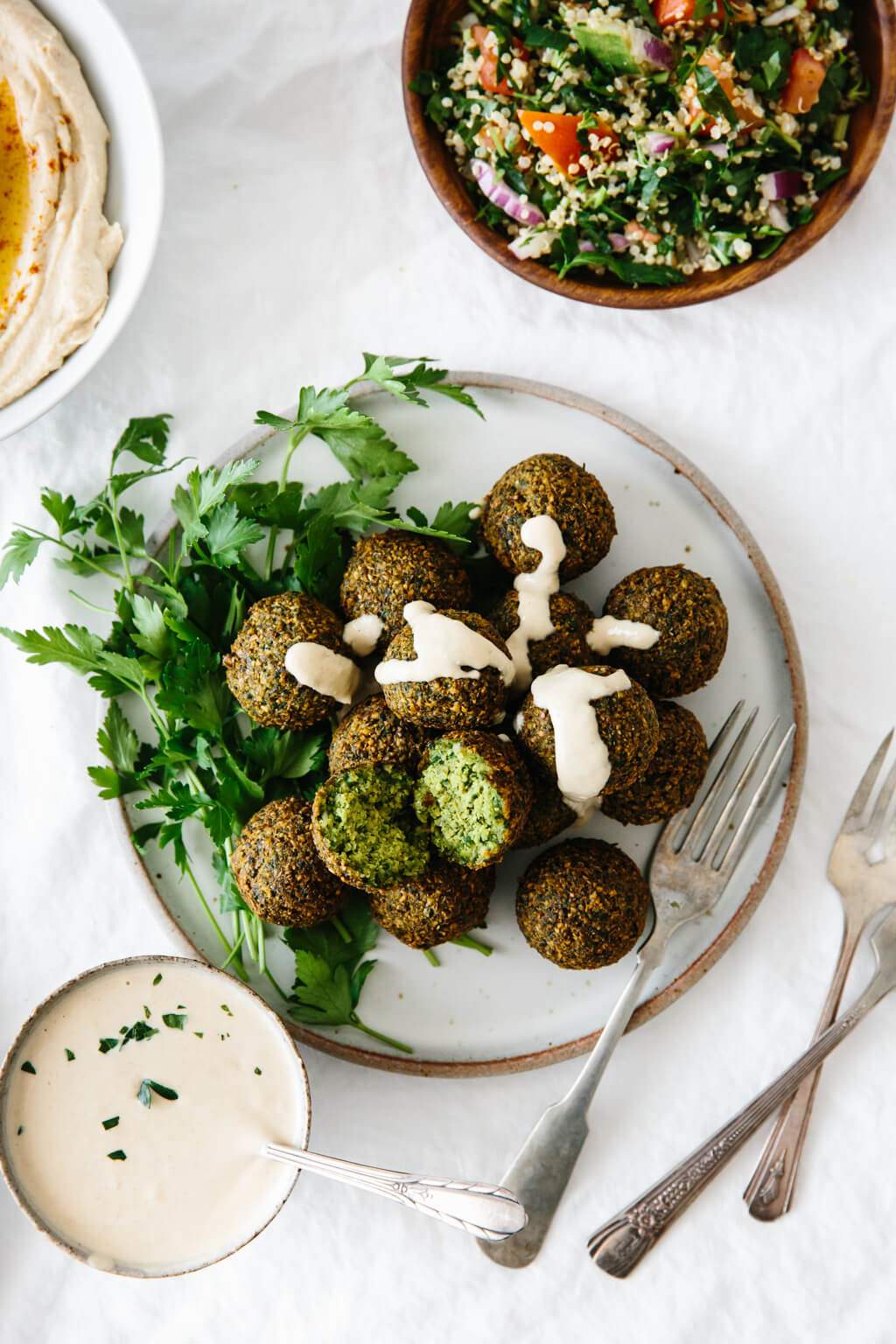 A plate of falafel served up with tahini sauce, hummus and tabbouleh.