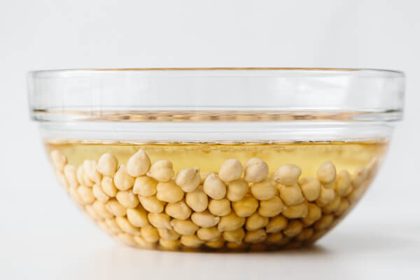 Dried chickpeas soaking in a bowl of water.
