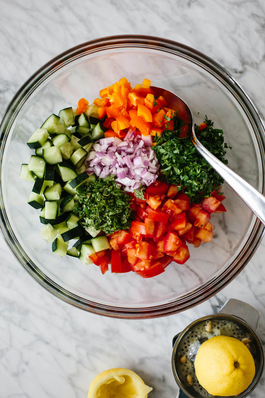 Israeli salad ingredients in a mixing bowl.