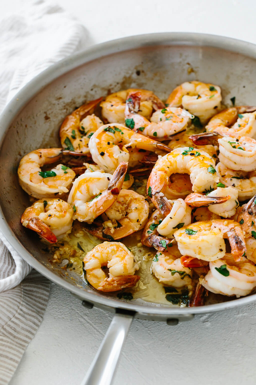 Shrimp sauteed in garlic and butter in a pan.