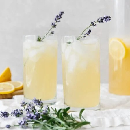 Two glasses of lavender lemonade on a table next to fresh lavender.