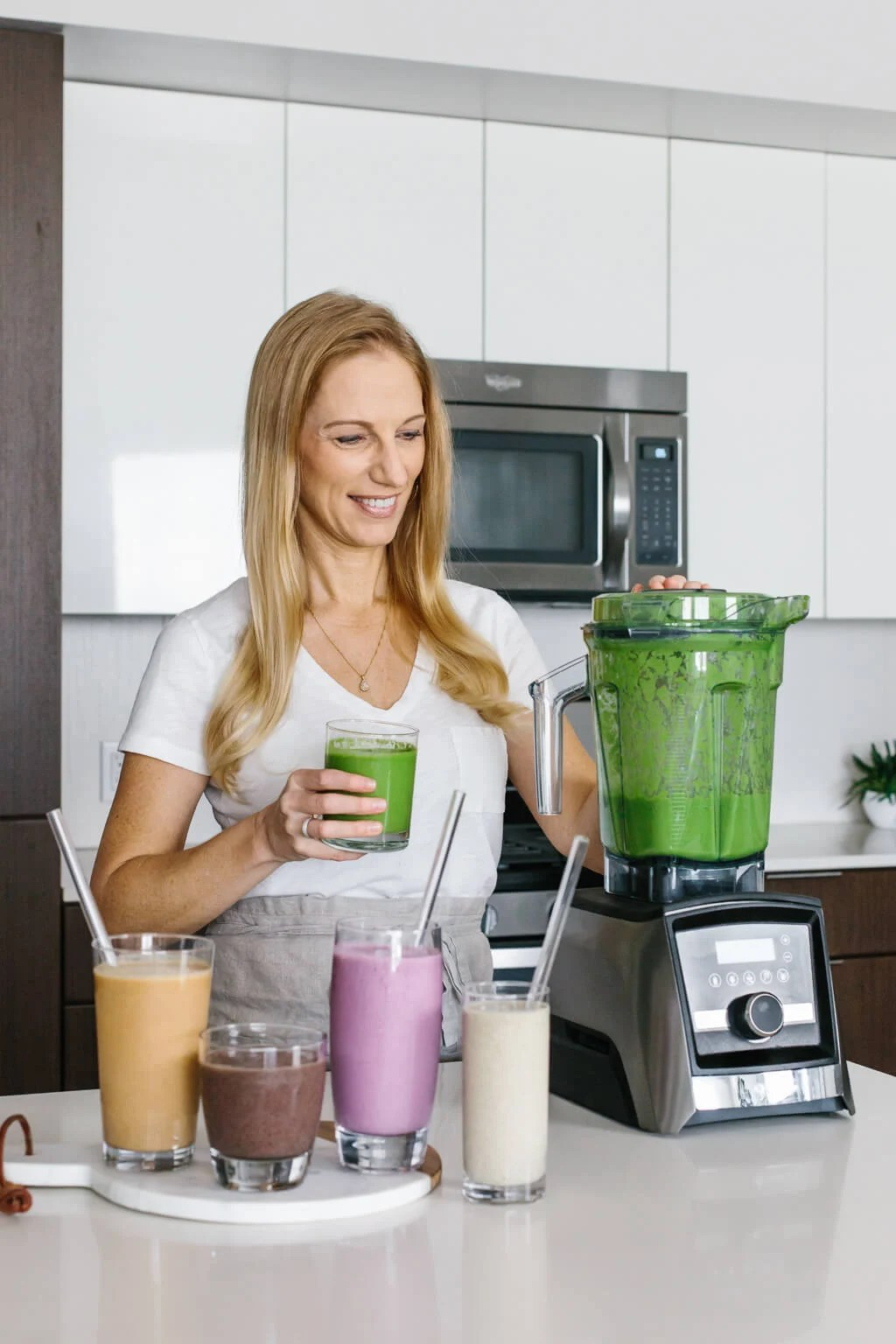 Lisa Bryan standing next to a Vitamix blender with different colored smoothies.