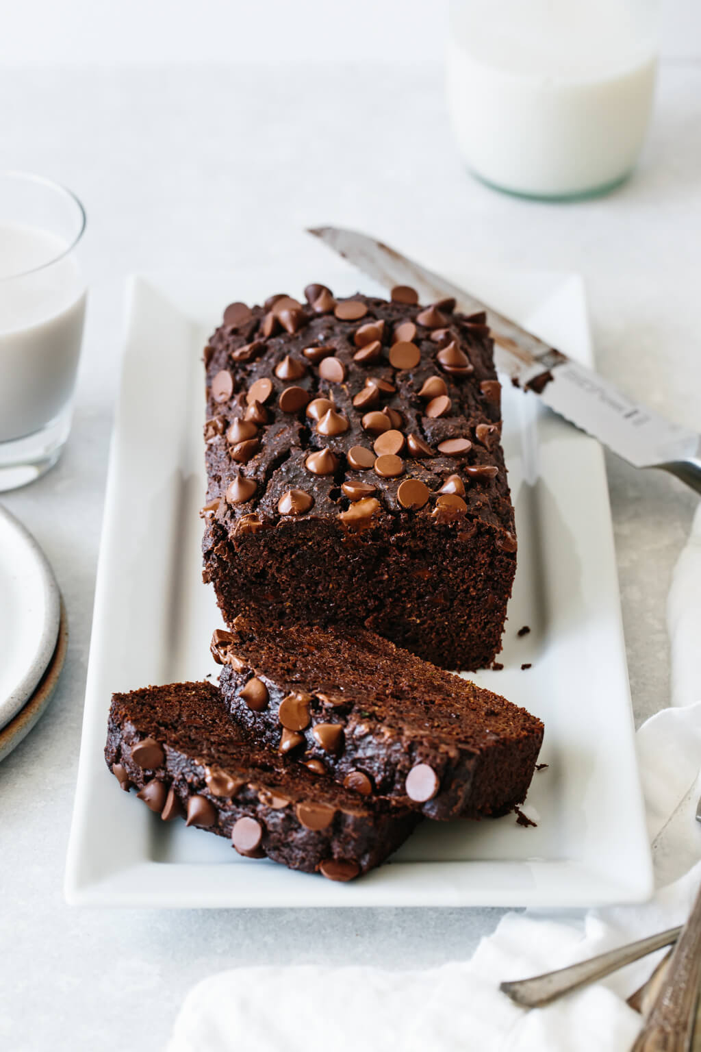 Paleo chocolate zucchini bread on a white serving platter.