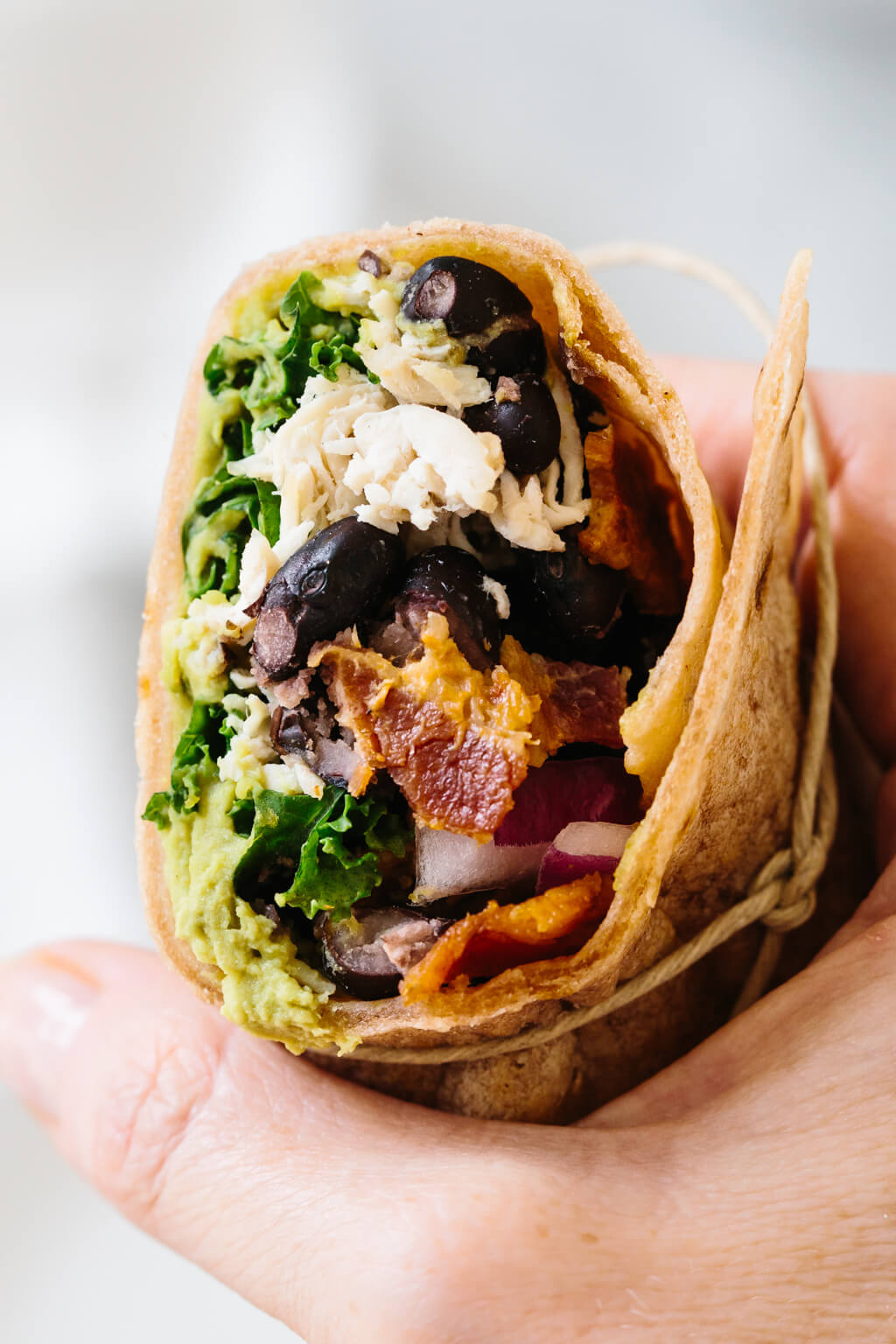 Chicken wrap cut in half and held in hand.