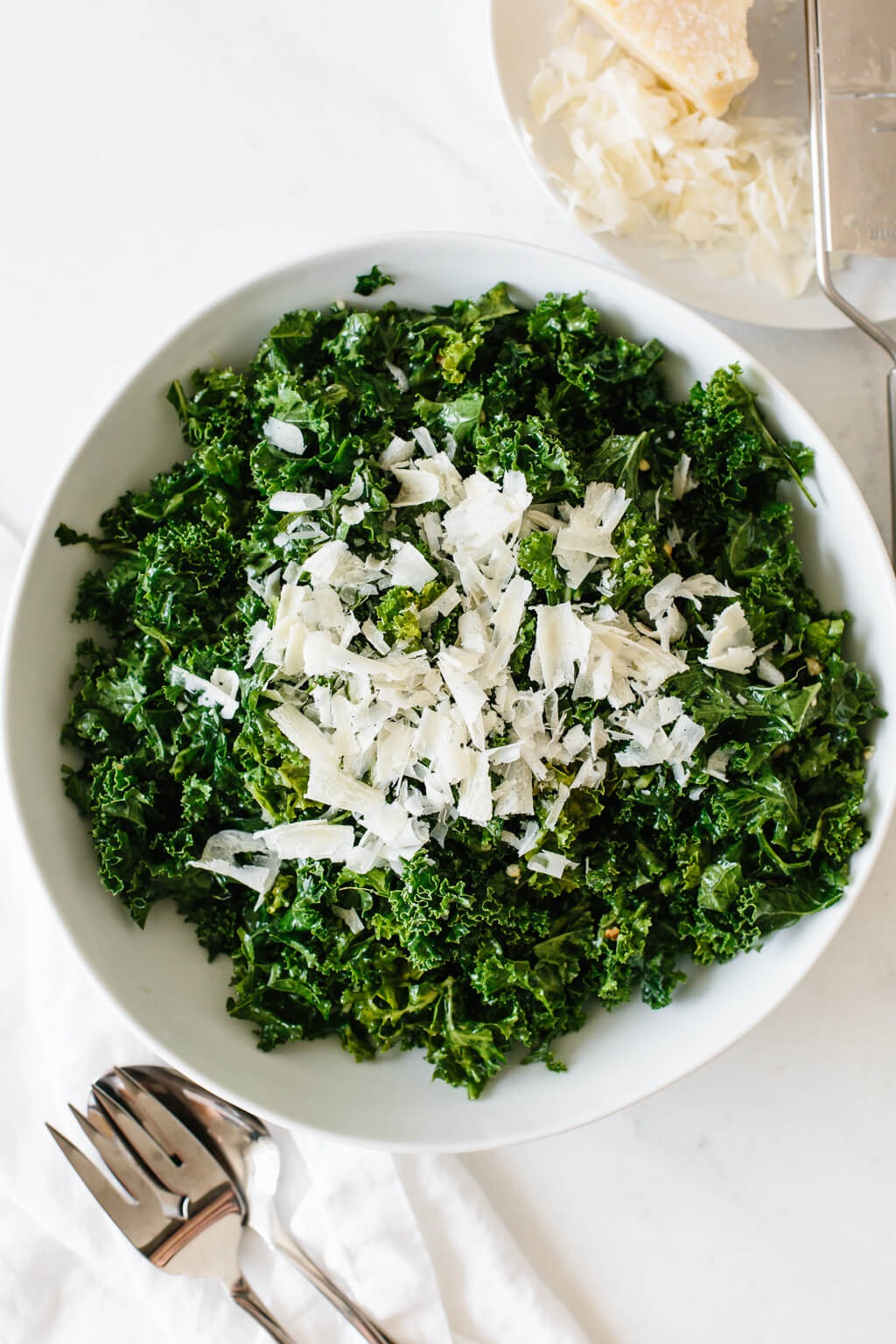 kale salad in a white bowl next to a bowl of shredded parmesan.