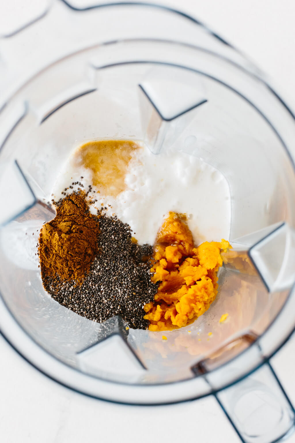 Ingredients to make pumpkin pie chia pudding in a blender.
