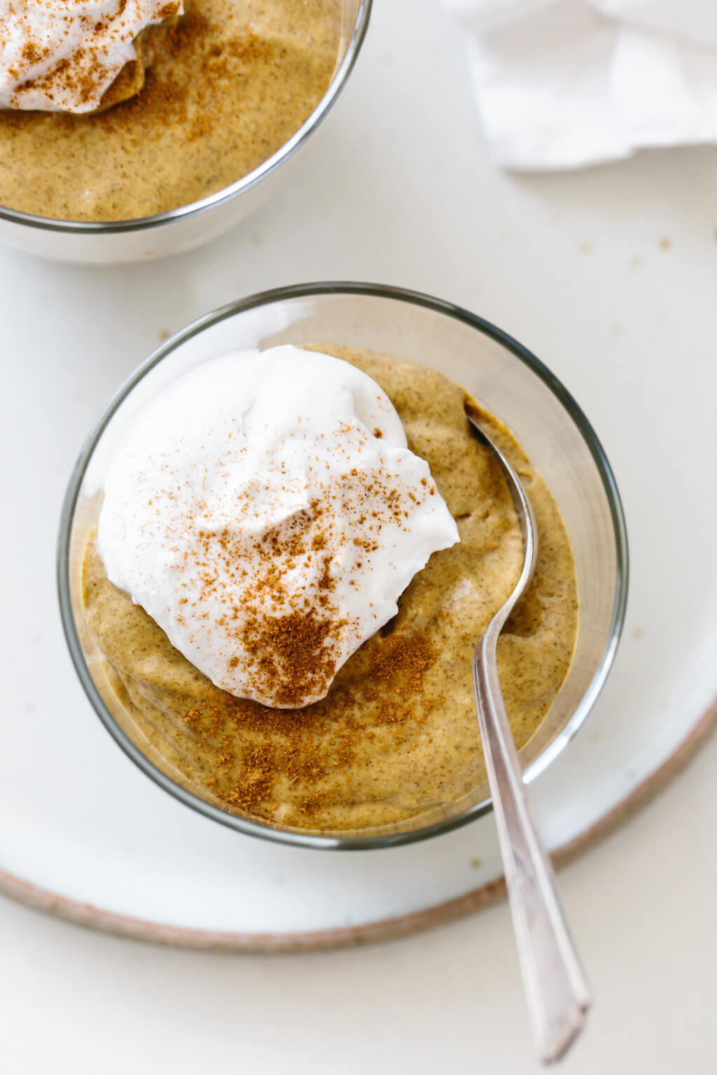 Pumpkin chia pudding in a glass jar with a dollop of whipped cream and cinnamon.