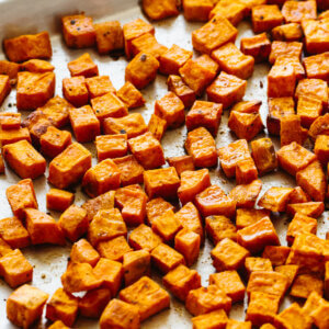 Roasted sweet potatoes on a sheet tray.