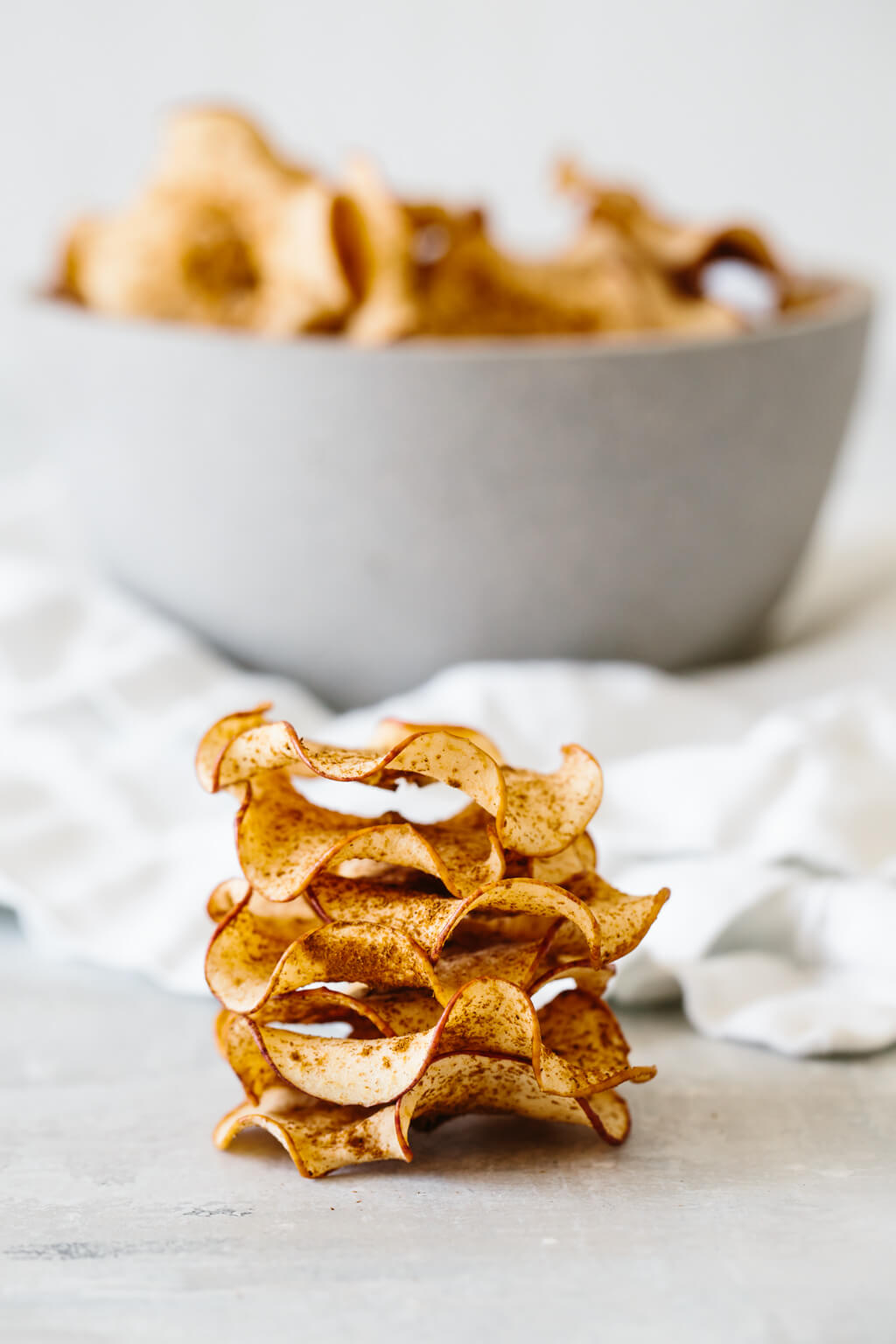 Crispy apple chips all stacked on top of each other.