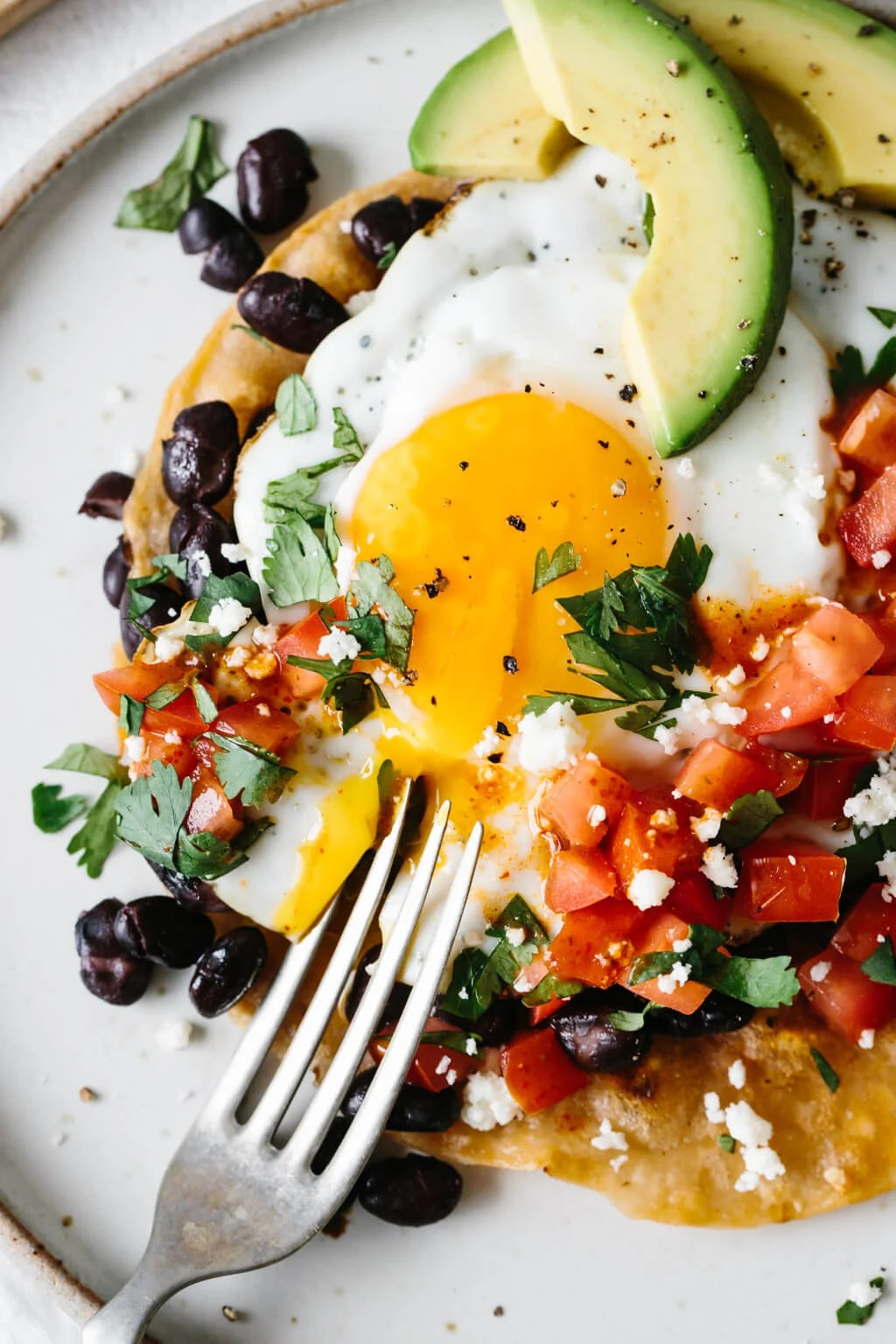 A fork broke open the yolk on a plate of huevos rancheros.