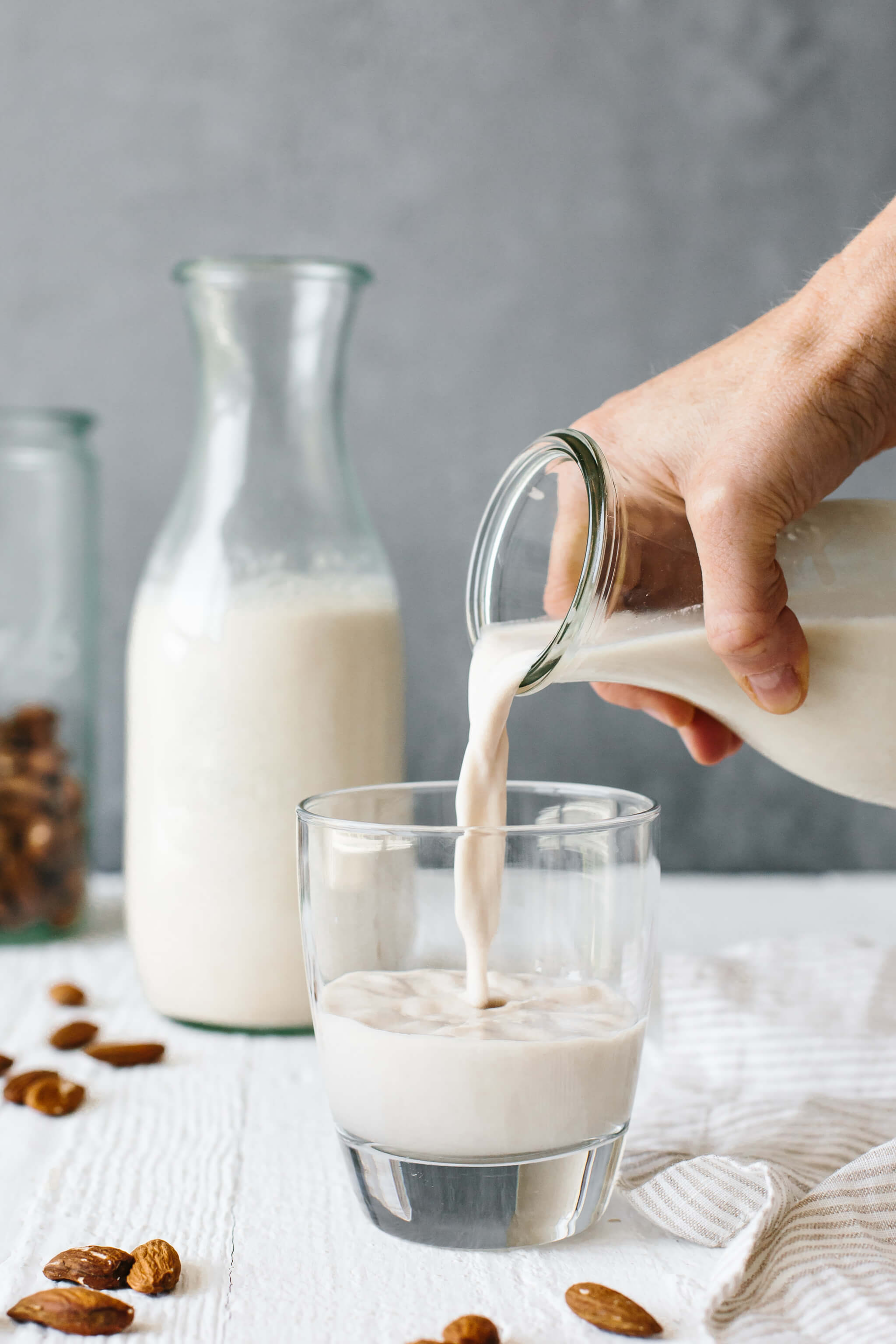 Pouring almond milk into a glass to drink.