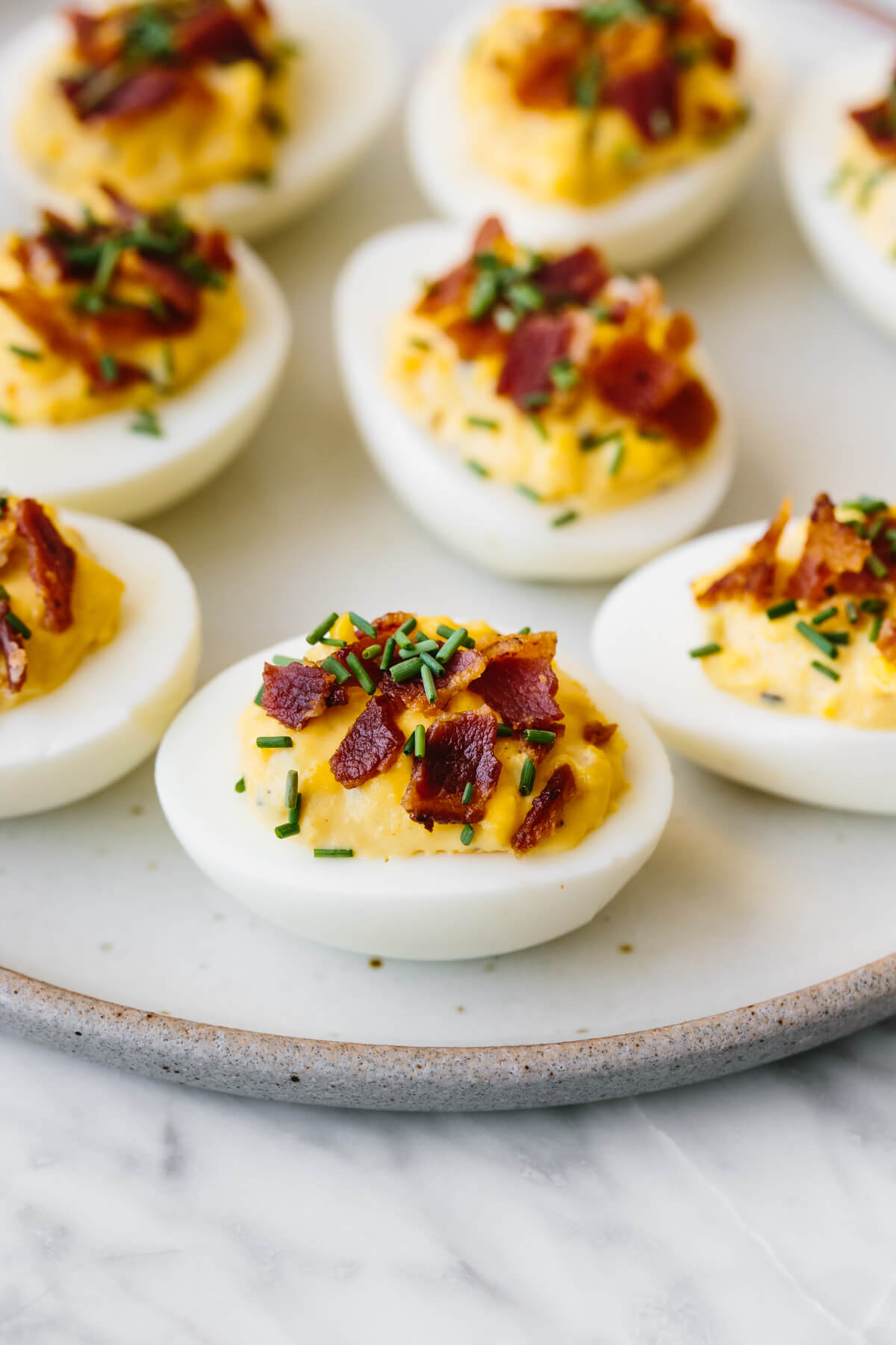 A plate of deviled eggs with bacon and chives sprinkled on top.