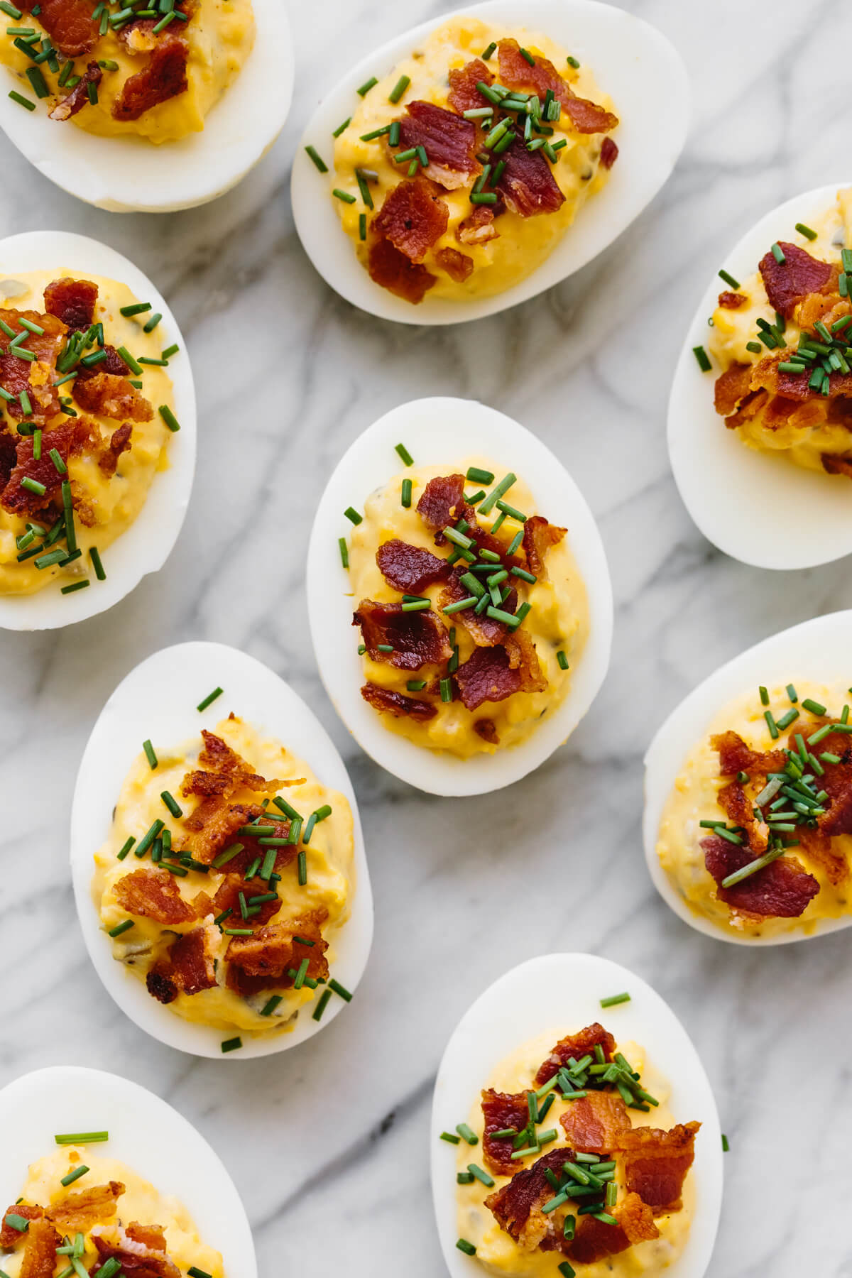 Several bacon deviled eggs on a marble counter.