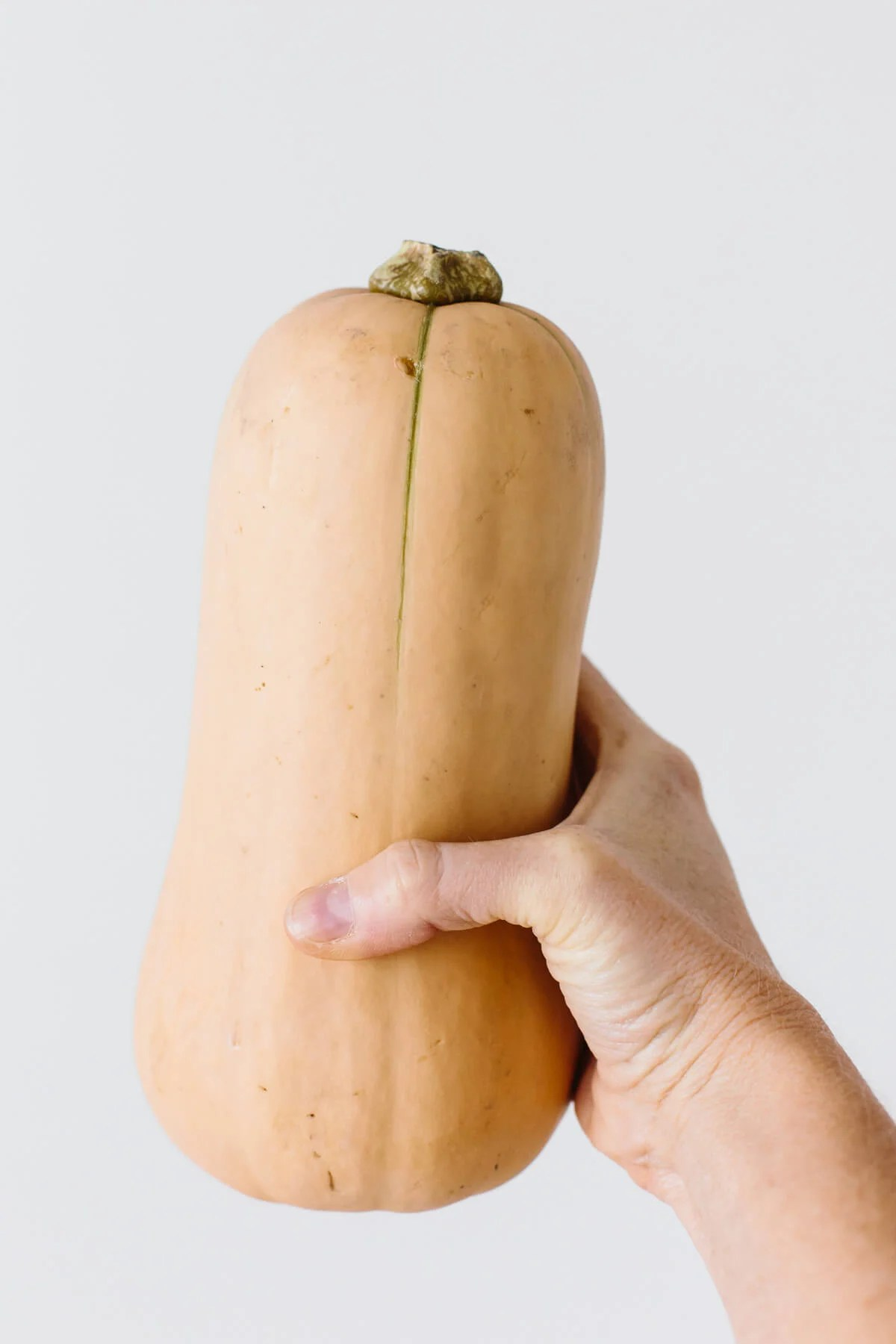 Holding butternut squash in hand.