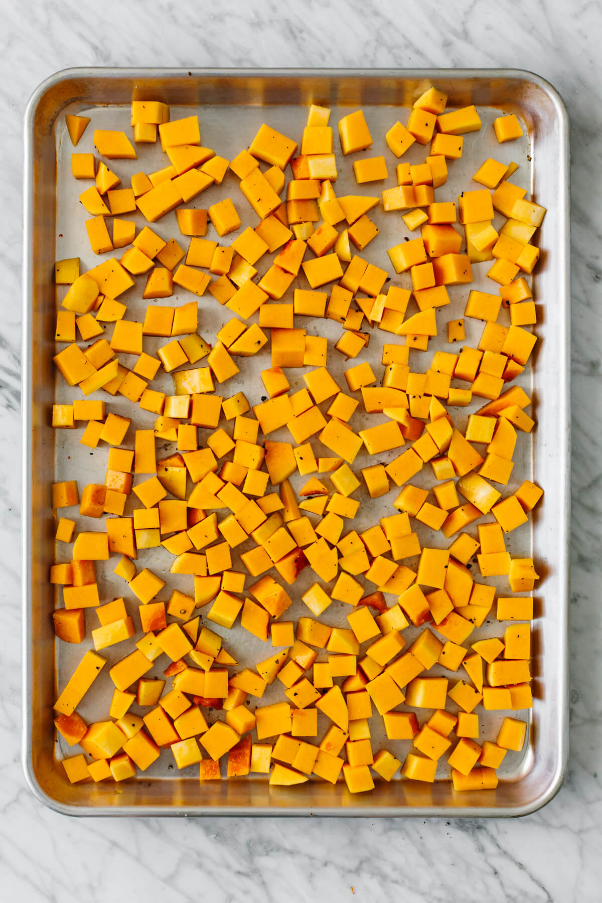 Diced and cubed butternut squash on a baking sheet.