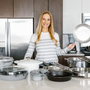 Girl holding stainless steel pan in front of various cookware pieces.