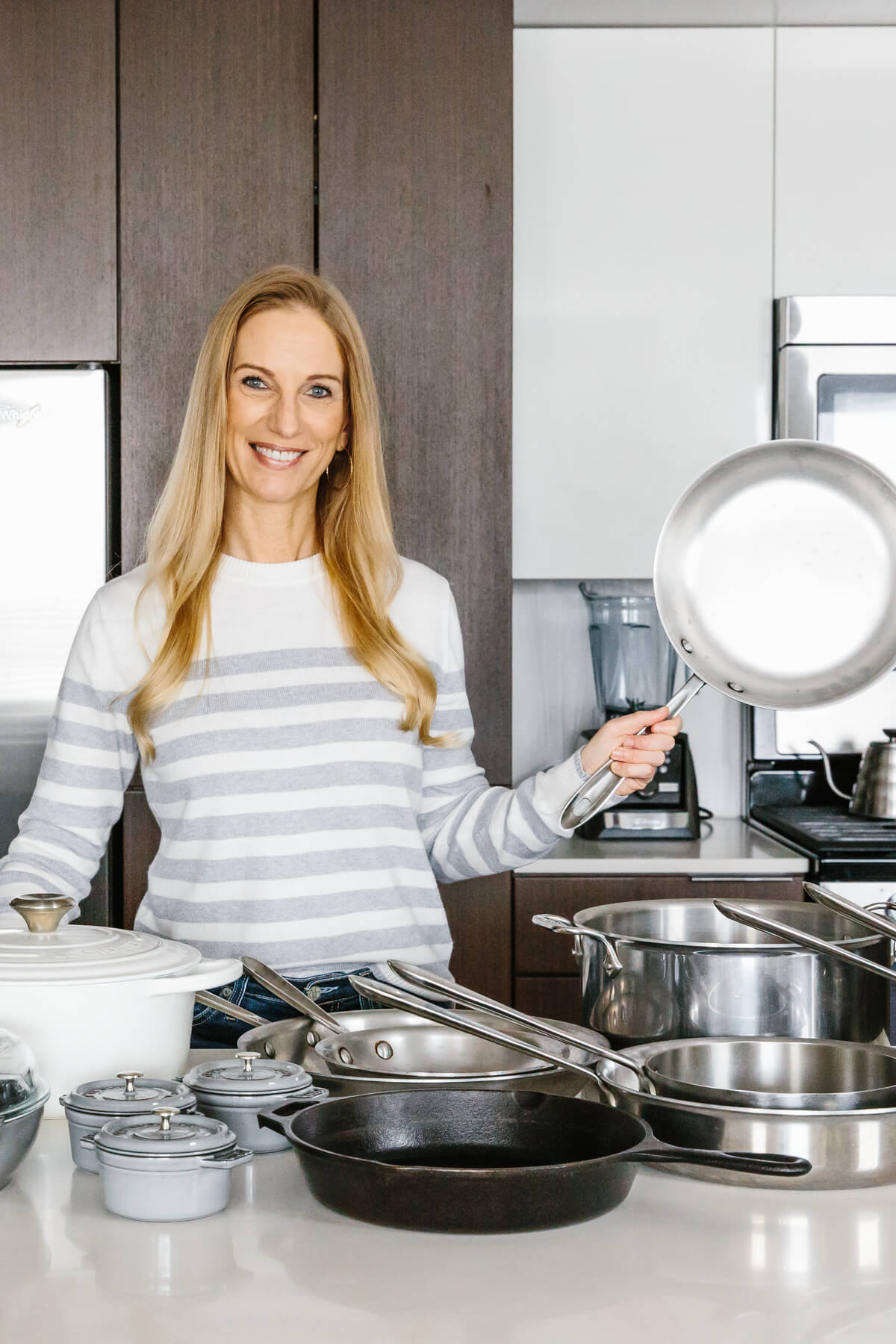 The best cookware types all on a counter with girl holding stainless steel pan.