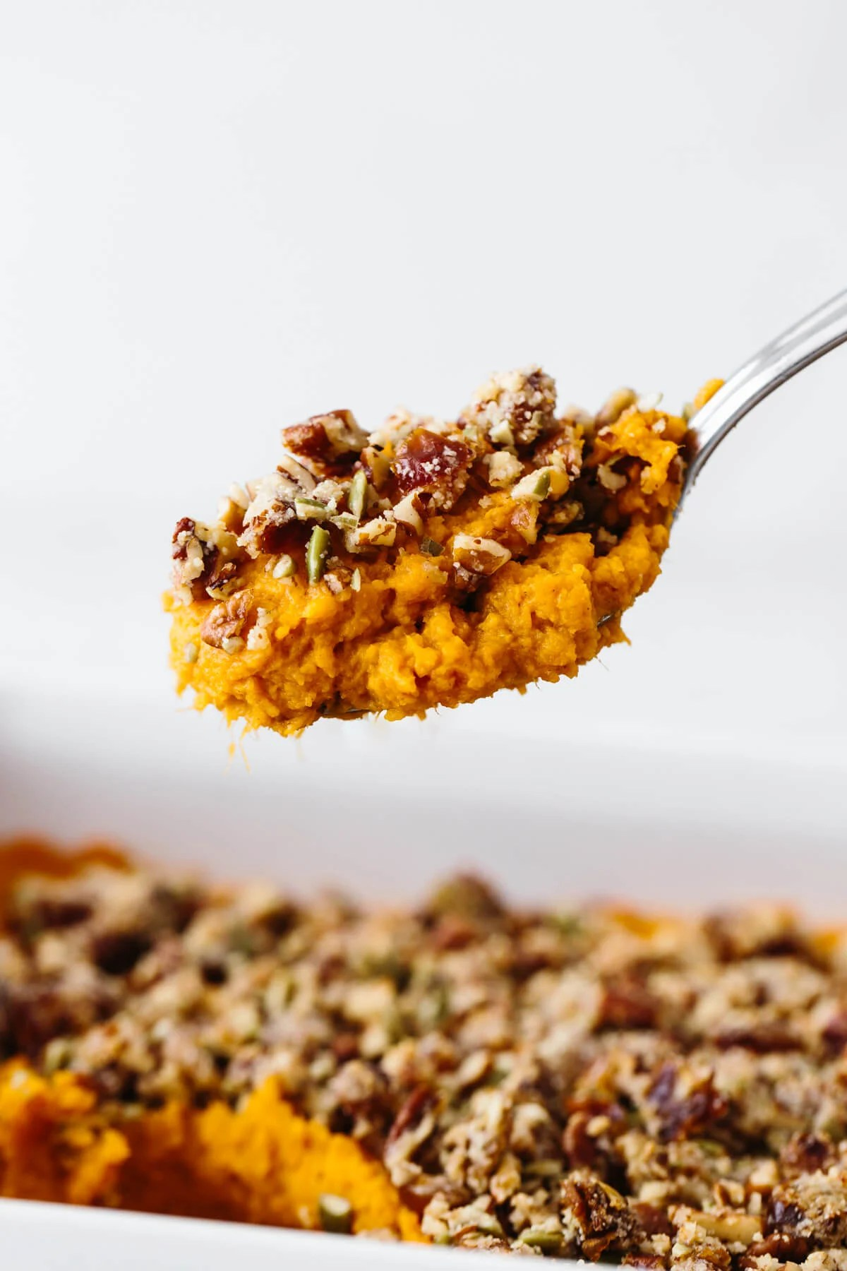A big scoop of the healthy sweet potato casserole on a spoon.
