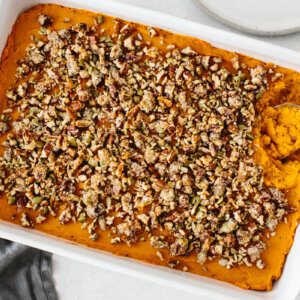 Mashed sweet potato topped with a pecan crumble in a white casserole dish.