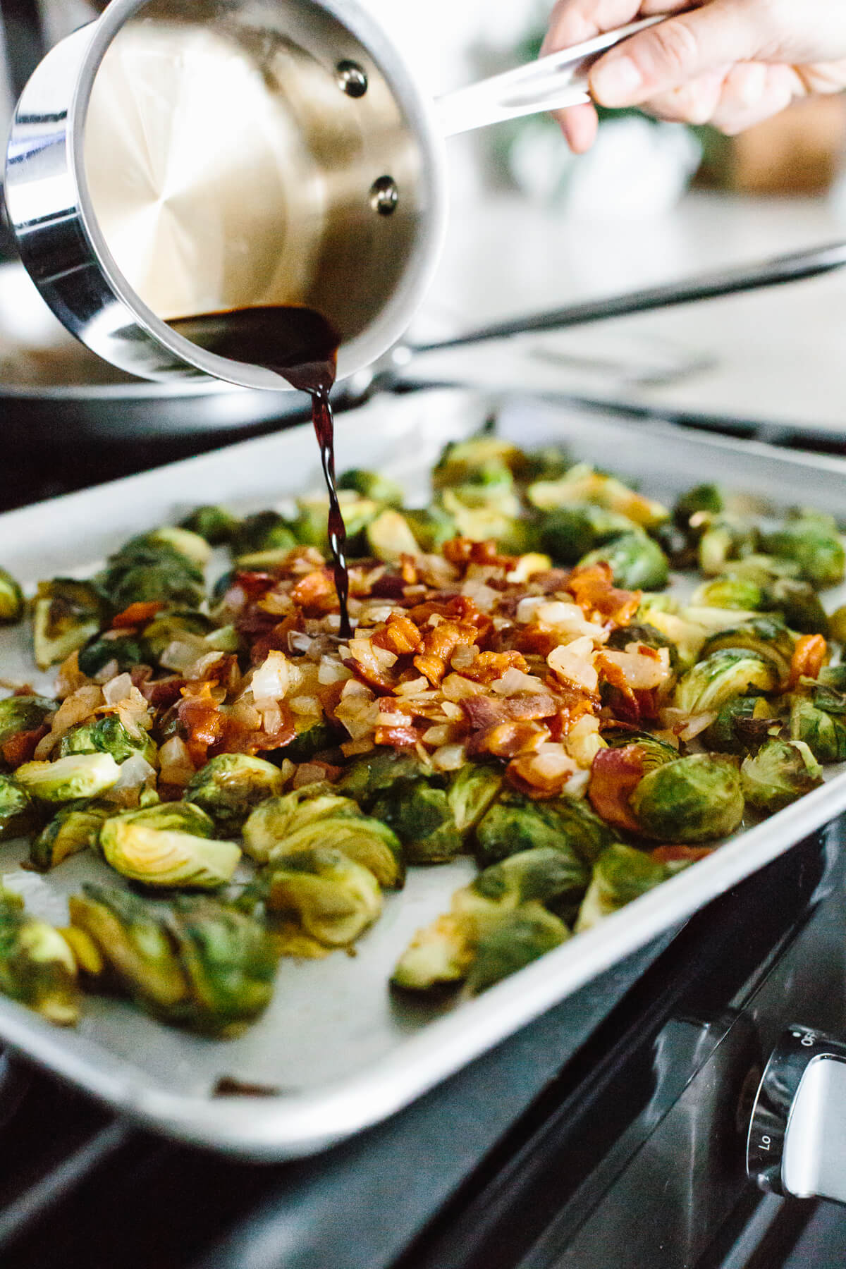 Pouring the balsamic glaze on the roasted brussels sprouts.