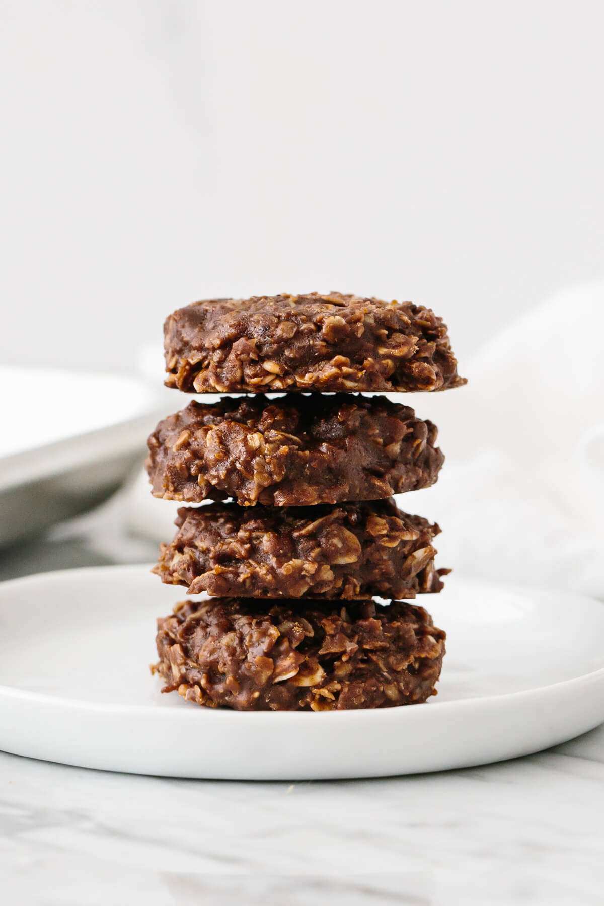 No bake cookies stacked on top of each other on a plate.