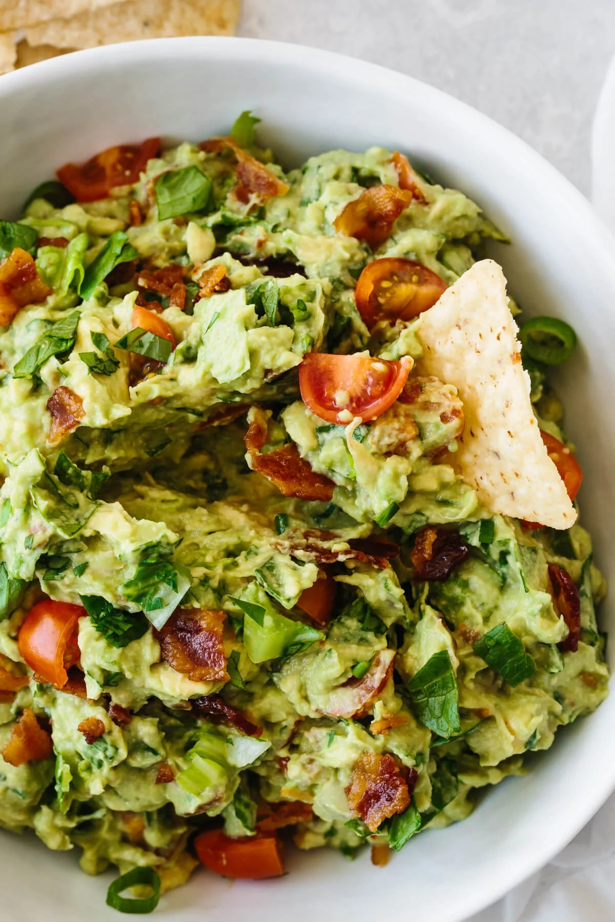 A tortilla chip taking a scoop of BLT guacamole.