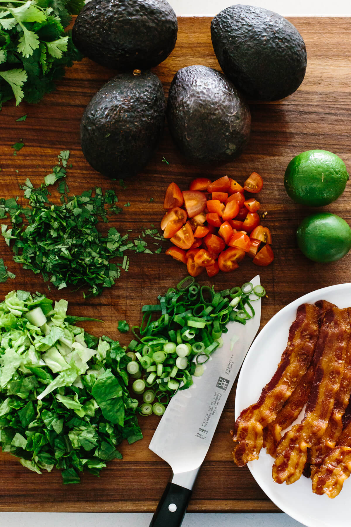 The ingredients for BLT guacamole on a cutting board.