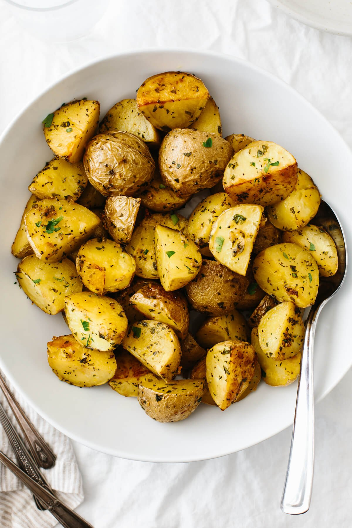 Garlic herb roasted potatoes in a white serving bowl.