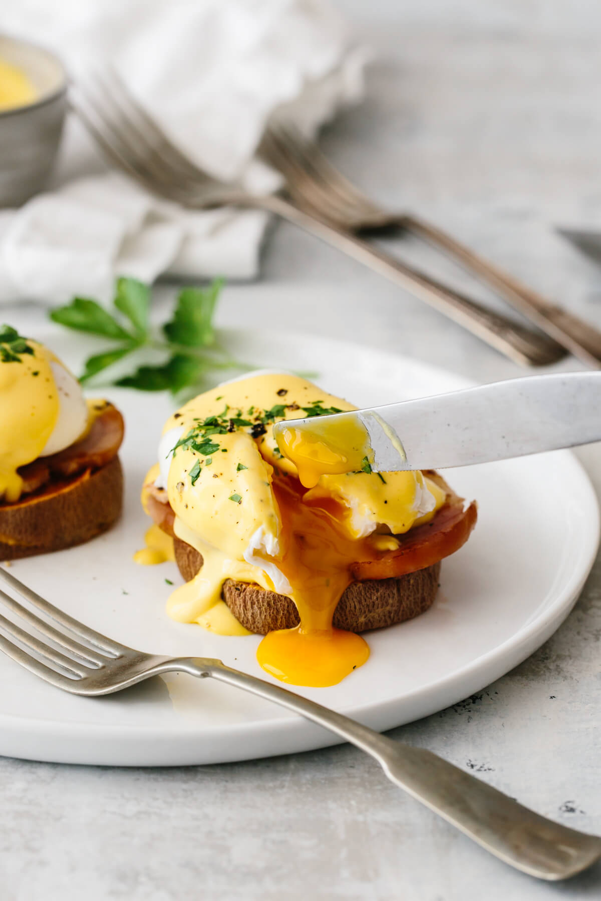 Healthy eggs benedict cut into with egg yolk oozing.