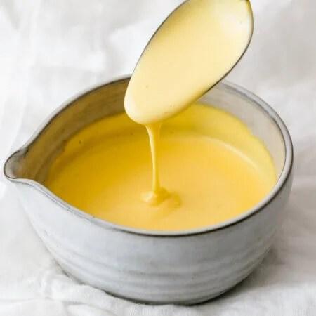 Hollandaise sauce dripping off a spoon.