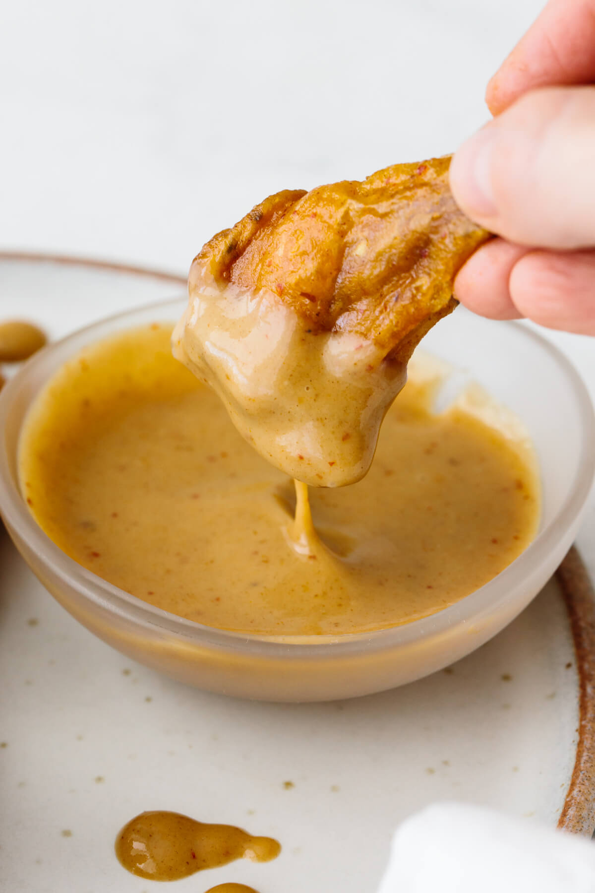 Honey mustard chicken wing dipping into honey mustard sauce.